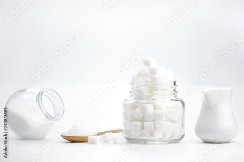 Fotografie, Obraz  Cube granulated sugar in a glass jar and  on wooden spoon for adding sweetness