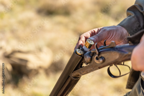 Hunter equips the retro double-barreled shotgun with cartridges, close up. Hunting season