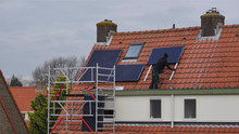 Solar Panels Placed On Roof By Worker