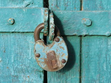 Old Rusty Padlock On Green Wooden Doors. Locked Gates, Home Security Concept
