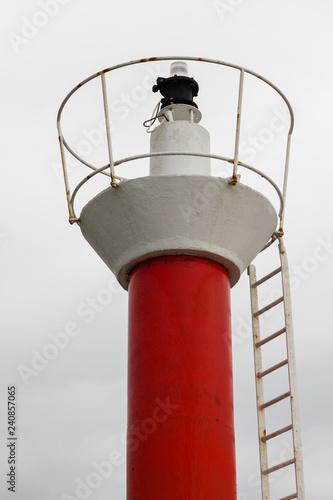 Fotografía  Faro rojo y blanco con luz roja de entrada a puerto