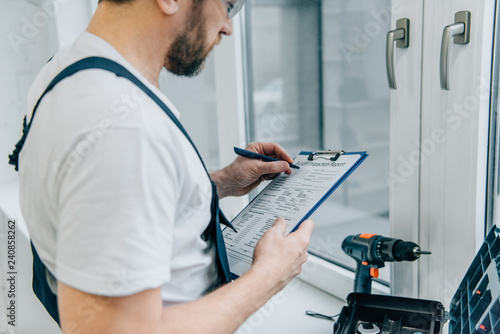 Fotografía  cropped shot of male handyman writing in clipboard and checking window