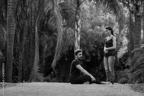 Fototapety, obrazy: Young woman talking to man sitting on grass in park. Couple chatting and enjoying leisure time in nature outdoors. Black and white photography