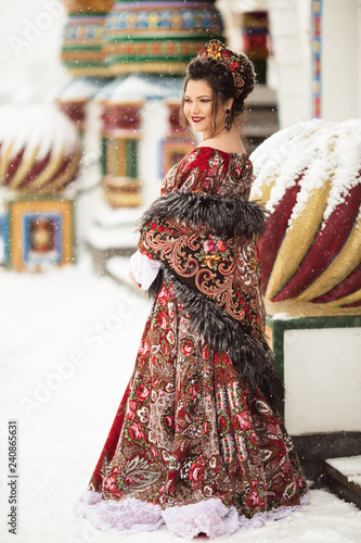 72332330fc8b4 Beautiful happy woman is wearing traditional russian dress in winter park