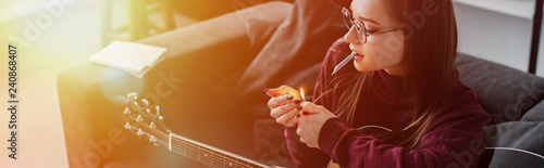 girl lighting marijuana joint and holding guitar at home with backlit and copy s Wallpaper Mural