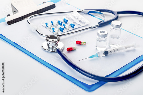 Fotografie, Obraz  Pills spilling out of pill bottle syringe thermometer and stethoscope on white b