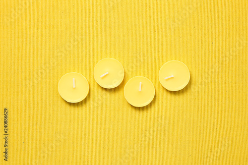 Yellow candles on yellow fabric background