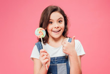 Smiling Child Holding Lollipop And Showing Thumb Up Isolated On Pink