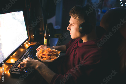 Photo  Gamer plays video games at home in the computer room, eats dishes and drinks beer