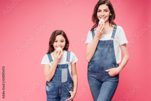 mom and daughter eating cupcakes with hands in pockets isolated on pink Canvas Print