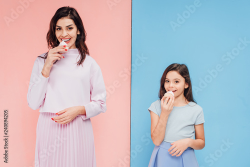 beautiful woman and child eating cupcakes and looking at camera on blue and pink Wallpaper Mural