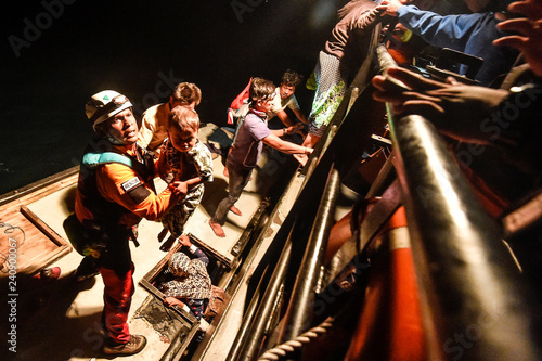 Rescue worker holds kid as he evacuates local residents at Sebuku