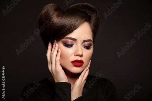 Fotobehang womenART Beauty Makeup and Hairstyle. Beautiful woman with red lipstick, long eyelashes, glitter eye shadow and retro hair style, manicured nails isolated on studio dark background.