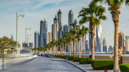 Waterfront promenade on the Palm Jumeirah with palms at road timelapse. Dubai, United Arab Emirates