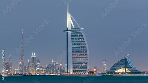Dubai skyline with Burj Al Arab hotel during sunset and day to night timelapse.