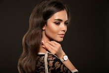 Elegant Lady With Watch On Hand. Beautiful Woman With Long Healthy Wavy Hair Style And Evening Makeup Posing In Studio On Dark Background.