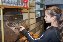 Girl With Old-time Cash Register In A Shop.
