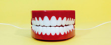 It's Never Too Late For Conscientious Dental Care. Dental Floss And Fake Teeth On A Yellow Background. Fun. Humor.