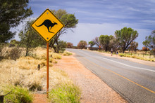 A Typical Road And Australian Road Sign Of Kangaroos Crossing, Taken At Uluru Or Ayers Rock In The Outback Desert Of Australia