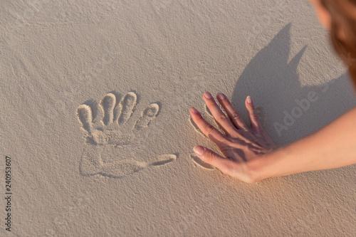Fényképezés  young woman doing Handprints in white sand