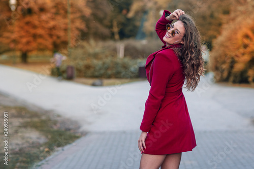 Fotografie, Obraz  Young long hair woman in red coat with sunglesses on the street in park
