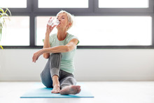 Mature Woman Drink Water After Exercise In Appartment At Rug With Window On Background