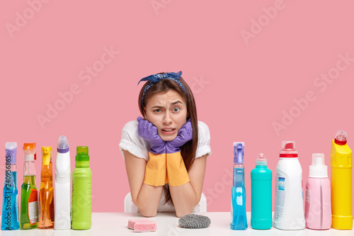 Fotografía  Photo of attractive woman holds chin, frowns face, wears headband, protective rubber gloves, surrounded with cleaning accessories, poses at desk, feels tired of housework