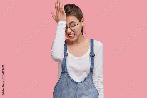 Fotografie, Obraz  Photo of dissatisfied young woman regrets wrong doing, keeps hand on forehead, clenches teeth, dressed in fashionable outfit, isolated over pink studio wall