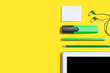 canvas print picture - row of business or education accessories. green pencils, headphones, paper stickers, markers and tablet pc lying on a yellow surface. concept of the office chancery and gadgets. free copyspace