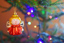 Cute Decorative Angel Girl Toy Hanging On Blurred Christmas Tree Branch With Copy Space For Text.  Merry Christmas And Happy New Year Concept.