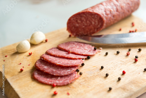 Fotografie, Obraz  sliced salami slices with spices and garlic on wooden Board, knife