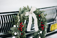 Classic Christmas Wreath On  Retro Car. Holiday Car Wreath. Retro Car Decorated With Christmas Wreath For Holidays.