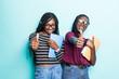 Leinwandbild Motiv Young afro american student girls show thumbs up and holding netobooks isolated on pastel blue background