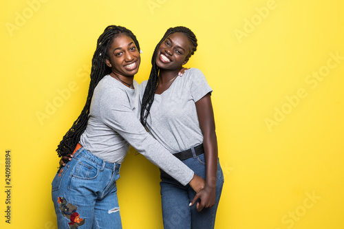 Fotografie, Obraz  Photo of affectionate lovely african womens stand closely hug each other embrace isolated over yellow background