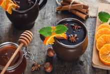 Hot Mulled Wine With Orange, Cinnamon, Honey And Anise On Wooden Background.