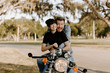 Precious Cute Leisure Lifestyle Portrait of Handsome Guy and Girl Beauty Being Silly Fun and Laughing while Riding Classic Motorcycle Bike While in Love