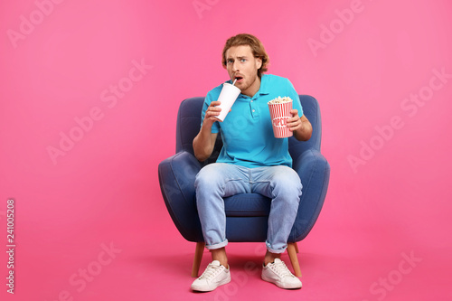 Emotional man with popcorn and beverage sitting in armchair during cinema show on color background