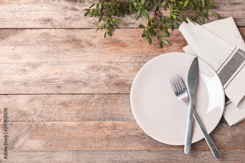 Beautiful table setting with cutlery, napkin and plate on wooden background, top view. Space for text