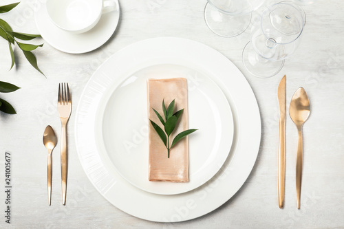 Beautiful table setting with cutlery, napkin and dinnerware on grey background, top view