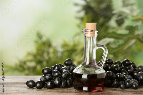Glass jug with wine vinegar and fresh grapes on wooden table against blurred background