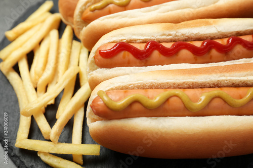 Delicious hot dogs and french fries on slate plate, closeup