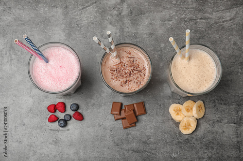 Glasses with different protein shakes and ingredients on grey background, top view