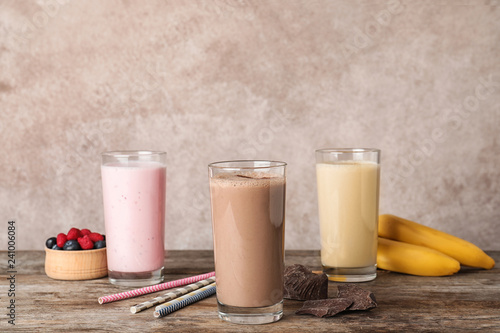 Glasses with different protein shakes and ingredients on table against color background
