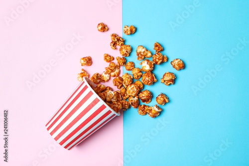 Overturned paper cup with caramel popcorn on color background, top view