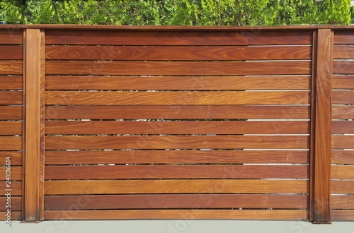 Fotografie, Obraz  The fence around the house of wooden planks and wooden pillars, based on a concr