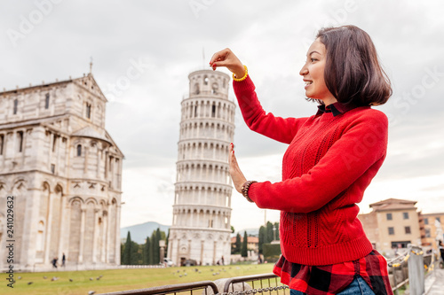 Fotografie, Obraz Young woman traveler making funny poses in front of the famous leaning tower in Pisa, Italy