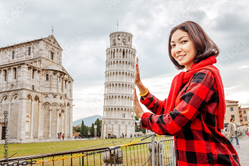 Fotomural Young woman traveler making funny poses in front of the famous leaning tower in Pisa, Italy