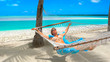 CLOSE UP: Young female tourist relaxing in a hammock right by the turquoise sea.