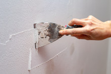 Stripping Old Paint From The Wall. Renovation And Painting Of Walls In The Apartment.
