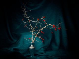 Winter red berries in a vase with turquoise fabric, light painting still life. Decorative.